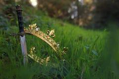 загадочное и волшебное фото кроны и шпаги короля золота в ландшафте древесин или поля Англии со светлым пирофакелом средневеково стоковая фотография rf