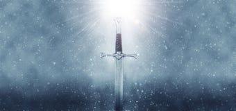 загадочное и волшебное фото серебряной шпаги над готической снежной черной предпосылкой средневековая концепция периода стоковые изображения