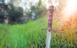 загадочное и волшебное фото серебряной шпаги над ландшафтом древесин или поля Англии со светлым пирофакелом средневековая концепц стоковое изображение
