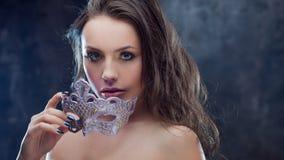 Загадочное и красивое брюнет с венецианской маской Стоковые Фото