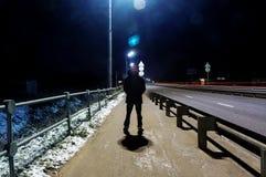Загадочный человек стоит самостоятельно в улице, среди автомобилей в пустом городе, дорога после дождя, прогулки weat улица ночи, стоковая фотография rf