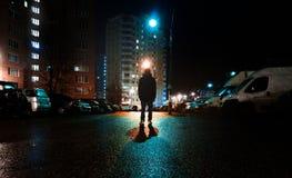 Загадочный человек стоит самостоятельно в улице, среди автомобилей в пустом городе, дорога после дождя, прогулки weat улица ночи, стоковые изображения rf