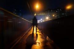 Загадочный человек стоит самостоятельно в улице, среди автомобилей в пустом городе, дорога после дождя, прогулки weat улица ночи, стоковое фото rf