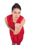 Загадочное брюнет в красном платье посылая поцелуй к камере стоковая фотография rf