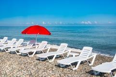 Загорать пластичные кровати и красный зонтик на пляже Стоковое Фото