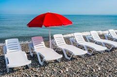 Загорать пластичные кровати и красный зонтик на пляже Стоковое Изображение