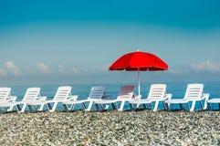 Загорать пластичные кровати и красный зонтик на пляже Стоковая Фотография RF