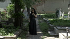 Загореванная вдова заполнила при скорба выходя от уведенной могилы супруга идя в переулок кладбища сток-видео