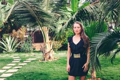 Загоренная девушка представляя против предпосылки ладоней Стоковые Фотографии RF