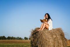 Загоренная девушка сидит на стоге сена стоковые фотографии rf