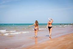 Загоренная женщина и девушка идя на seashore Стоковые Фотографии RF