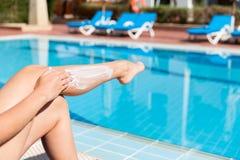 Загоренная женщина сидит бассейном и прикладывает sunblock для защиты ее кожи от загара Фактор предохранения от Солнца внутри стоковая фотография rf