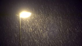 Загоренная общественная лампа в темном проливном дожде ночи видеоматериал