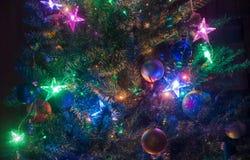 Загоренная рождественская елка накаляя на темной предпосылке Стоковое Изображение RF