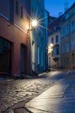 Загоренная узкая улица на ноче в городке Таллина старом Стоковые Изображения RF