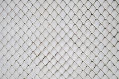 Загородка звена цепи на предпосылке стены белого цемента Стоковые Изображения RF