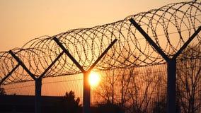 Загородка колючей проволоки тюрьмы на заходе солнца Яркая свобода 4k силуэта солнца и деревьев акции видеоматериалы