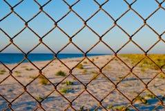 Загородка решетки металла на солнце лета голубого неба моря проволочной изгороди пляжа Стоковое Изображение