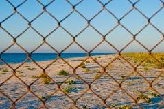Загородка решетки металла на солнце лета голубого неба моря проволочной изгороди пляжа Стоковое Фото
