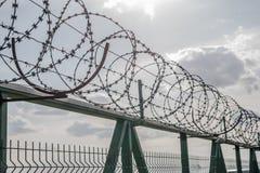 Загородка с колючей проволокой на предпосылке неба Стоковое Фото