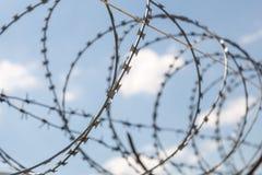 Загородка с предохранением от колючей проволоки бритвы против предпосылки голубого неба Концепция диктатуры и тирании стоковая фотография rf
