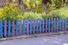 Загородка голубой сирени декоративная деревянная около зеленой травы и цветков около дороги Стоковые Фото