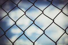 Загородка звена цепи с предпосылкой голубого неба в ретро Стоковые Изображения