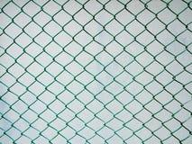 Загородка звена цепи с предпосылкой стены цемента Стоковые Фотографии RF