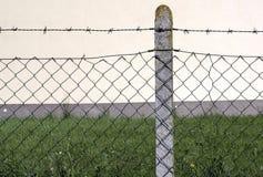 Загородка и столбец колючей проволоки Стоковые Изображения