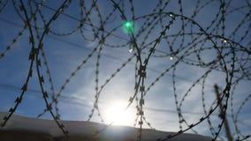 Загородка колючей проволоки на тюрьме, слепимости солнца на предпосылке голубого неба акции видеоматериалы