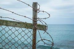 Загородка колючей проволоки на clifftop океана стоковая фотография