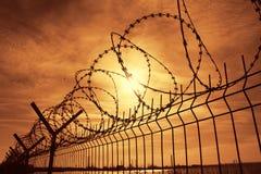 Загородка колючей проволоки тюрьмы на заходе солнца стоковые изображения rf