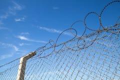 Загородка металла с колючей проволокой над голубым небом Стоковые Фотографии RF