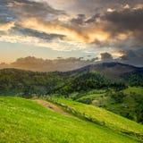 Загородка на луге горного склона в горе на восходе солнца Стоковое Изображение RF