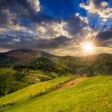 Загородка на луге горного склона в горе на заходе солнца Стоковое фото RF