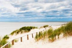 Загородка на дюне на взморье с бурными облаками видимыми. Стоковые Фотографии RF