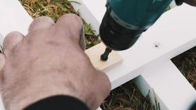 Загородка assambles работника деревянная на зеленой траве используя отвертку акции видеоматериалы