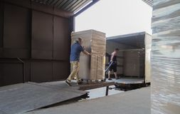 Загрузка и доставка тележки Мужские работники нагружают товары в картонных коробках на тележке стоковые изображения