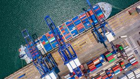 Загрузка контейнеровоза и разгружать в глубокий морской порт, воздушный взгляд сверху логистического дела перевозок из страны имп стоковая фотография