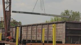 Загрузка трубы профиля краном на козлах в товарный вагон, металл нагрузок в складе, большом кране на козлах