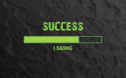 Загрузка успеха написанная в зеленом тексте на каменной предпосылке стоковые изображения