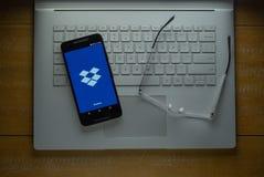 Загрузка app Dropbox на телефоне андроида в темной комнате стоковые фото