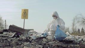 Загрязнение окружающей среды, исследователь Hazmat в защитный костюм собирает сор в сумке отброса для исследования на хламе акции видеоматериалы