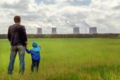 загрязнение проблема отброса пущи сброса относящая к окружающей среде Отец и сын смотря на излучения завода Стоковое Изображение RF