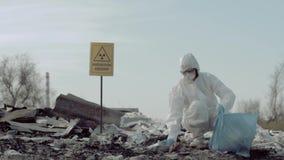 Загрязнение радиации, ученый Hazmat в защитную одежду собирает погань в сумке отброса для рассматривать на старье акции видеоматериалы