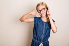 задне вызовите меня Милая предназначенная для подростков девушка со смартфоном показывая звонку меня стоковые фотографии rf