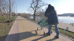 Задний взгляд бездомного человека нажимая магазинную тележкау видеоматериал