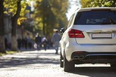 Задний взгляд белого автомобиля припаркованный на зоне города пешеходной на предпосылке запачканных силуэтов людей идя вдоль зеле стоковые фото
