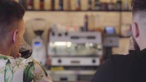 Задний взгляд 2 взрослых людей clink стекла сидя на усмехаться счетчика бара Расслабленные мужские друзья охлаждая совместно видеоматериал