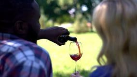 Задний взгляд вина счастливых пар лить в стекле, годовщина торжества на открытом воздухе стоковые фото